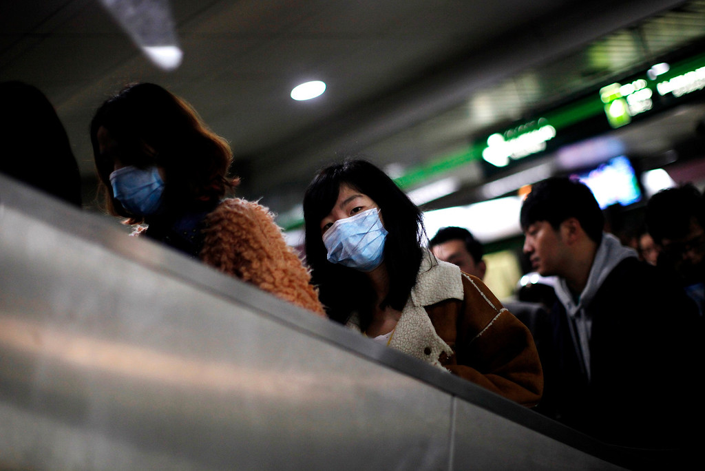 Description of . A woman wears a face mask inside a subway station in Shanghai, April 5, 2013. Chinese authorities were slaughtering birds at a poultry market in the financial hub Shanghai as the death toll from a new strain of bird flu mounted to six on Friday, spreading concern overseas and sparking a sell-off on Hong Kong's share market. State news agency Xinhua said the Huhuai market for live birds in Shanghai had been shut down and birds were being culled after authorities detected the H7N9 virus from samples of pigeons in the market. All of the 14 reported infections from the H7N9 bird flu strain have been in eastern China and at least four of the dead are in Shanghai, a city of 23 million people and the showpiece of China's vibrant economy. REUTERS/Carlos Barria