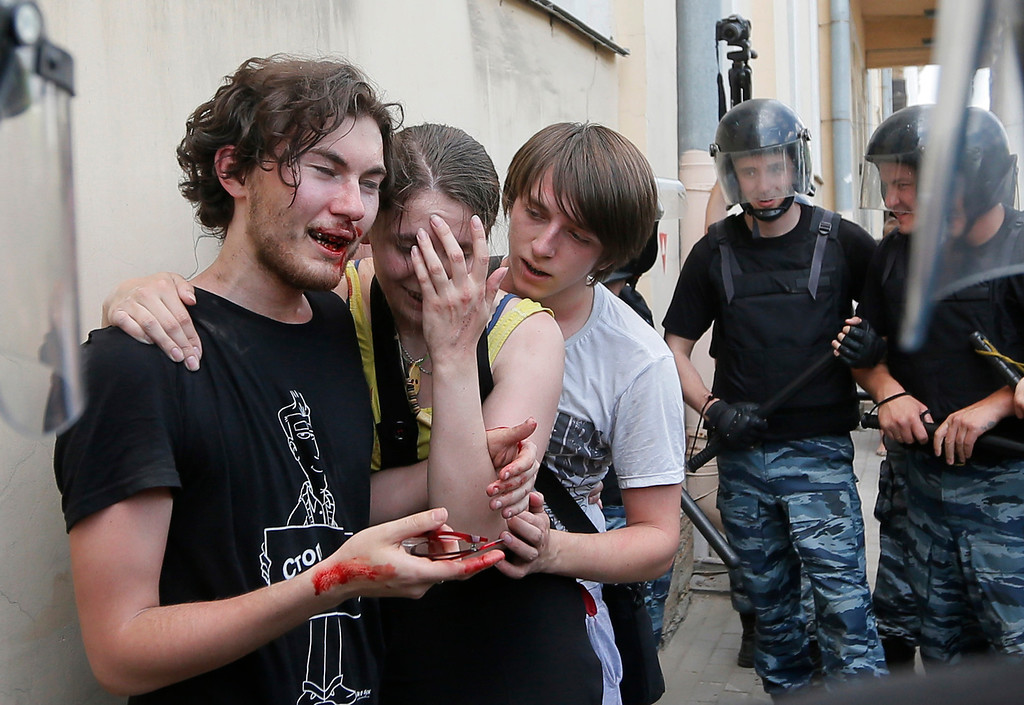 Description of . Riot police (OMON) guard gay rights activists who have been beaten by anti-gay protesters during an authorized gay rights rally in St.Petersburg, Russia, Saturday, June 29, 2013.  Police detained several gay activists, who were outnumbered by the protesters. Dozens of gay activists had to be protected by police as they gathered for the parade, which proceeded with official approval despite recently passed legislation targeting gays. (AP Photo/Dmitry Lovetsky)