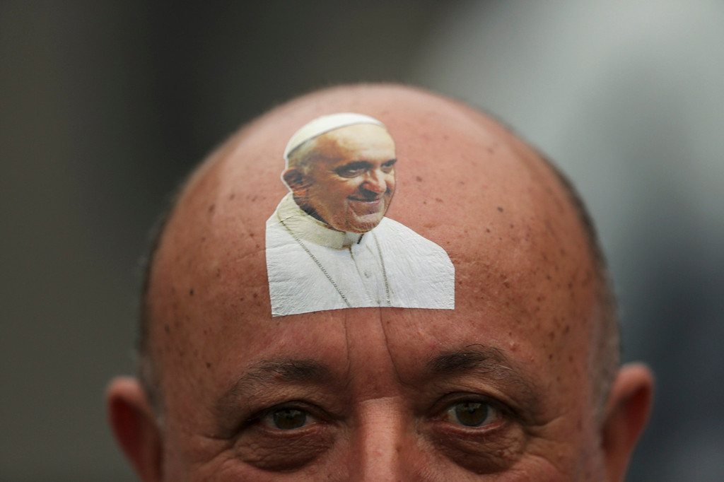 Description of . A Catholic faithful with a sticker bearing an image of Pope Francis on his forehead looks on while waiting for the Pope to arrive in Copacabana beach in Rio de Janeiro, July 25, 2013. Pope Francis is on the fourth day of his week-long visit for World Youth Day.             REUTERS/Ueslei Marcelino
