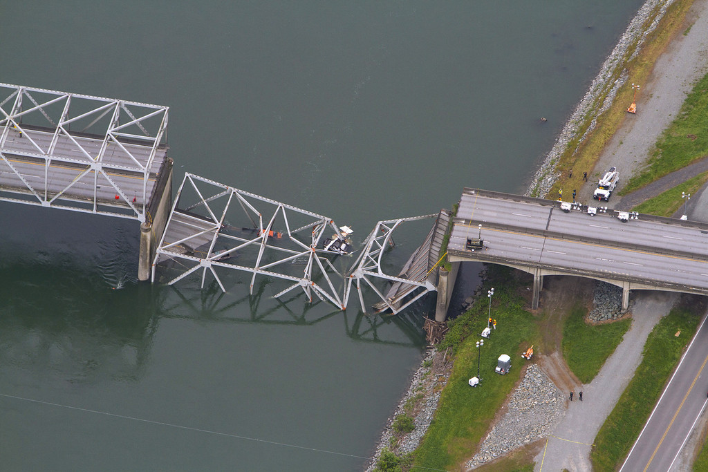 Description of . A collapsed section of the Interstate 5 bridge over the Skagit River is seen in an aerial view Friday, May 24, 2013. Part of the bridge collapsed Thursday evening, sending cars and people into the water when a an oversized truck hit the span, the Washington State Patrol chief said. Three people were rescued from the water. Washington Gov. Jay Inslee on Friday declared a state of emergency in three counties around the bridge, saying that the bridge collapse has caused extensive disruption, impacting the citizens and economy in Skagit, Snohomish and Whatcom Counties.  (AP Photo/The Seattle Times, Mike Siegel)