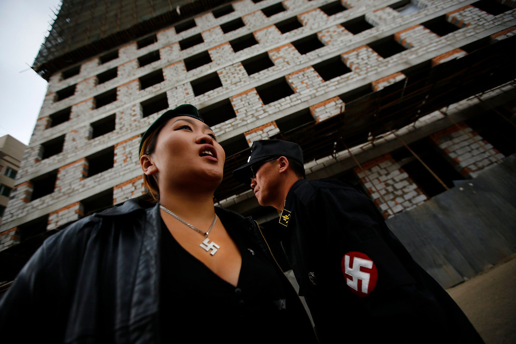 Description of . Ariunbold and Uranjargal (L), leaders of the Mongolian neo-Nazi group Tsagaan Khass, stand next to a construction site in Ulan Bator June 22, 2013. The group has rebranded itself as an environmentalist organisation fighting pollution by foreign-owned mines, seeking legitimacy as it sends Swastika-wearing members to check mining permits. Over the past years, ultra-nationalist groups have expanded in the country and among those garnering attention is Tsagaan Khass, which has recently shifted its focus from activities such as attacks on women it accuses of consorting with foreign men to environmental issues, with the stated goal of protecting Mongolia from foreign mining interests. This ultra-nationalist group was founded in the 1990s and currently has 100-plus members. Picture taken June 22, 2013. REUTERS/Carlos Barria