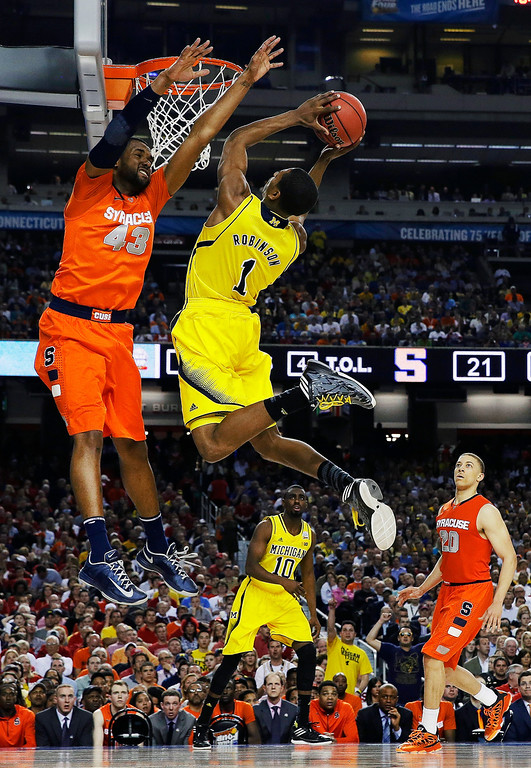 Description of . Michigan's Glenn Robinson III (1) shoots as Syracuse's James Southerland defends during the first half of an NCAA Final Four tournament college basketball semifinal game Saturday, April 6, 2013, in Atlanta. (AP Photo/David J. Phillip)