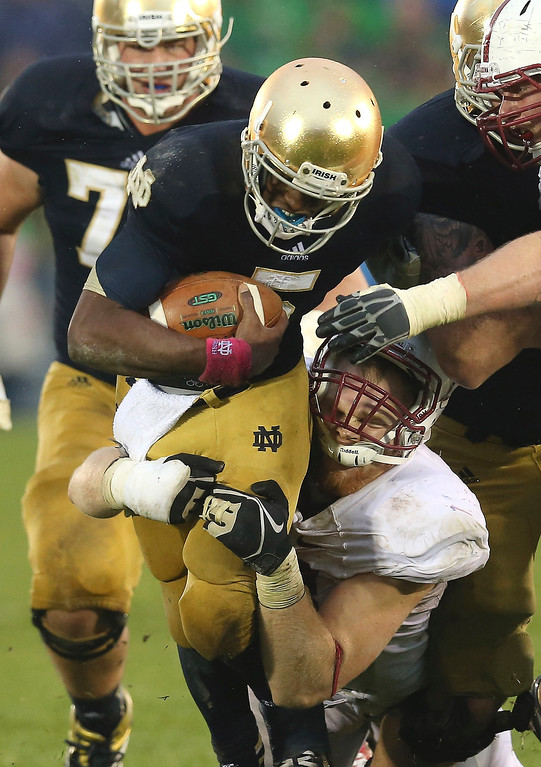 Description of . Everett Golson #5 of the Notre Dame Fighting Irish is tackled by Trent Murphy #93 of the Standford Cardinal at Notre Dame Stadium on October 13, 2012 in South Bend, Indiana. Notre Dame defeated Stanford 20-13 in overtime. (Photo by Jonathan Daniel/Getty Images)