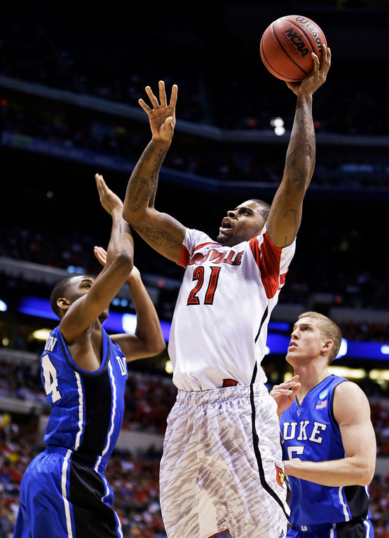 Description of . Louisville forward Chane Behanan (21) shoots under pressure from Duke guard Rasheed Sulaimon (14) and Duke forward Mason Plumlee (5) during the first half of the Midwest Regional final in the NCAA college basketball tournament, Sunday, March 31, 2013, in Indianapolis. (AP Photo/Michael Conroy)