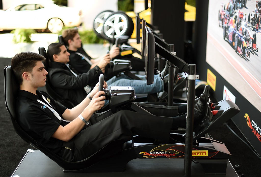 Description of . Men try out Pirelli driving simulators during the second press preview day at the 2014 New York International Auto Show  April 17, 2014  in New York at the Jacob Javits Center. AFP PHOTO / Timothy A. CLARY/AFP/Getty Images