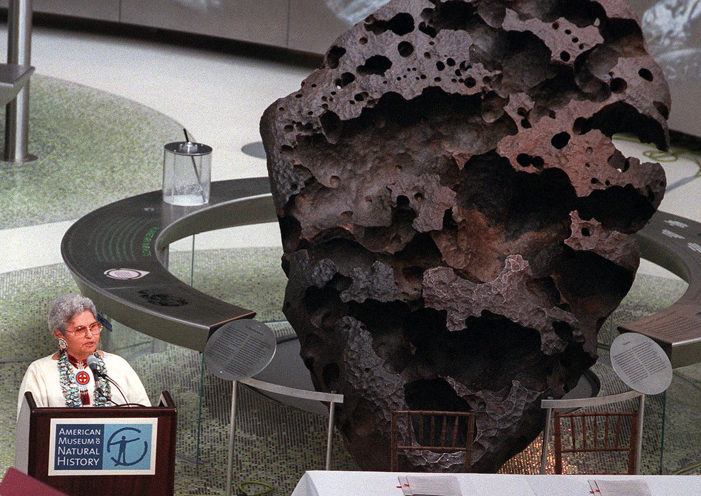 Description of . The 16-ton Willamette Meteorite rests behind Kathryn Harrison, chairwoman of Oregon's Grand Ronde Tribal Council, as talks to reporters Thursday, June 22, 2000, at New York's American Museum of Natural History.  It was discovered near Portland nearly a century ago by a miner and purchased a few years later by a New York philanthropist who donated it to the museum.  The museum heads and the tribal council signed an agreement to share custody of the 10,000-year-old meteorite that's a centerpiece of the museum's new planetarium. The tribal council claimed ownership of the rock, which holds tremendous religious significance to the Clackamas tribe, part of the council. (AP Photo/Keith Bedford)