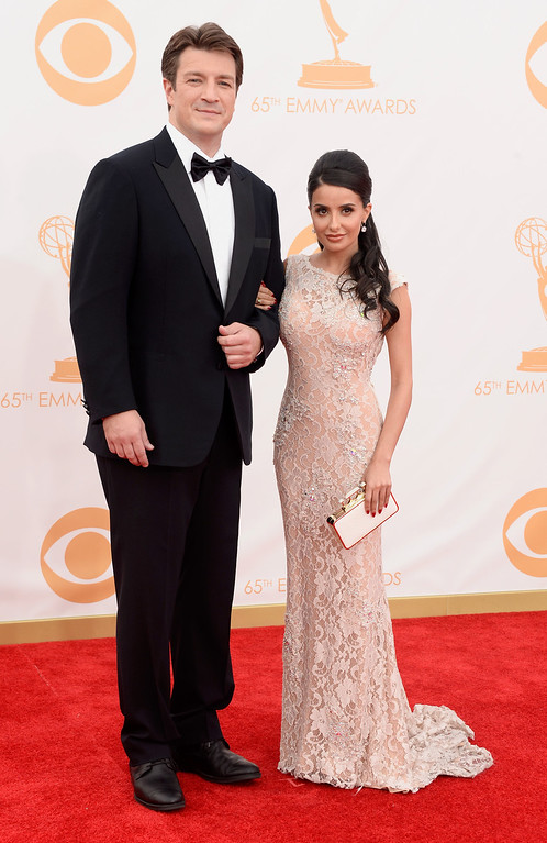 Description of . Actor Nathan Fillion (L) and actress Mikaela Hoover arrive at the 65th Annual Primetime Emmy Awards held at Nokia Theatre L.A. Live on September 22, 2013 in Los Angeles, California.  (Photo by Frazer Harrison/Getty Images)