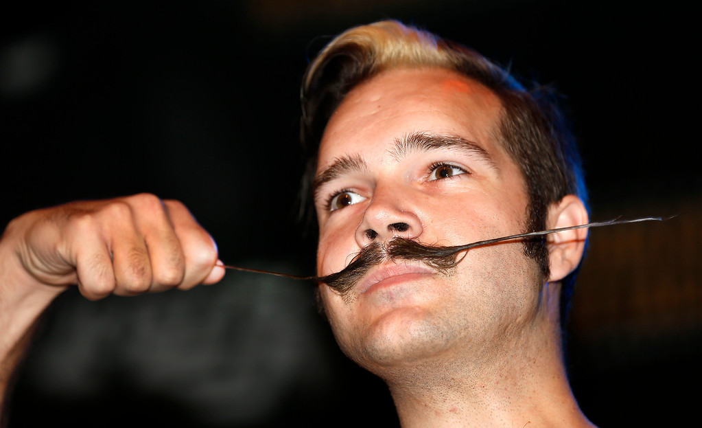 Description of . Brian Werle shows off his mustache while competing in the English Moustache division during the fourth annual Just For Men National Beard and Moustache Championships Saturday, Sept. 7, 2013, in New Orleans. Contestants competed in 18 different categories including Dali, full beard natural and sideburns.  (AP Photo/Susan Poag)