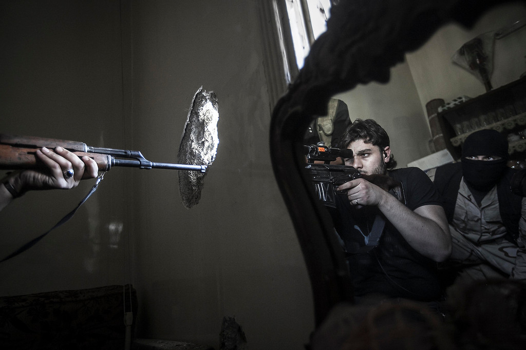 Description of . In this Monday, Oct. 29, 2012 photo, a rebel sniper aims at a Syrian army position, seen with another rebel fighter reflected in a mirror, in a residential building in the Jedida district of Aleppo, Syria. Syrian fighter jets pounded rebel areas across the country on Monday with scores of airstrikes that anti-regime activists called the most widespread bombing in a single day since Syria's troubles started 19 months ago. (AP Photo/Narciso Contreras)