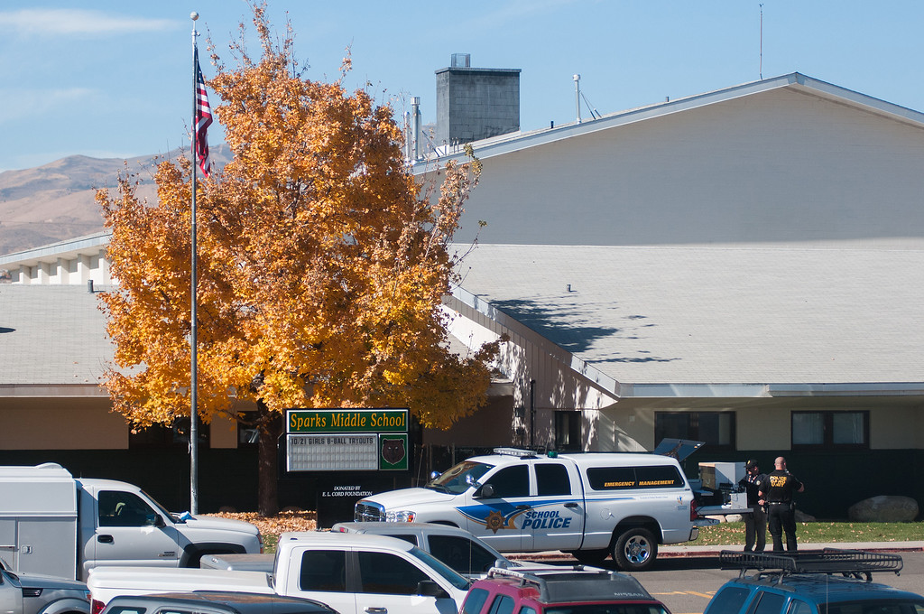 Description of . Police are staged in front of Sparks Middle School after a shooting in Sparks, Nev. on Monday, Oct. 21, 2013 in Sparks, Nev.  (AP Photo/Kevin Clifford)