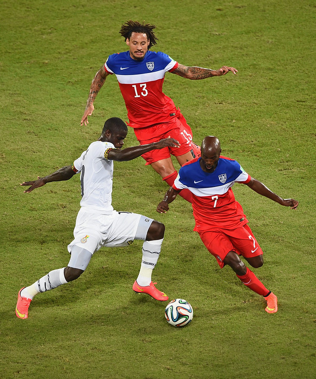Description of . Jonathan Mensah of Ghana and DaMarcus Beasley of the United States battle for the ball as Jermaine Jones of the United States looks on during the 2014 FIFA World Cup Brazil Group G match between Ghana and the United States at Estadio das Dunas on June 16, 2014 in Natal, Brazil.  (Photo by Laurence Griffiths/Getty Images)