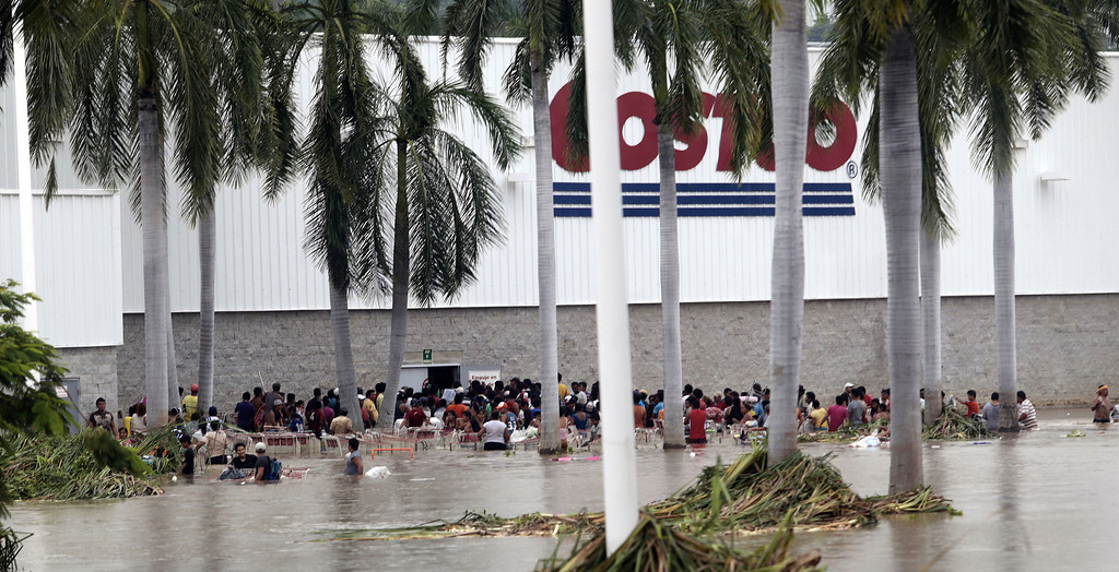 Description of . Residents loot a suupermarket in Acapulco, state of Guerrero, Mexico, on September 17, 2013 as heavy rains hit the country. Mexican authorities scrambled Tuesday to launch an air lift to evacuate tens of thousands of tourists stranded amid floods in the resort of Acapulco following a pair of deadly storms. The official death toll rose to 47 after the tropical storms, Ingrid and Manuel, swarmed large swaths of the country during a three-day holiday weekend, sparking landslides and causing rivers to overflow in several states.  Pedro PARDO/AFP/Getty Images