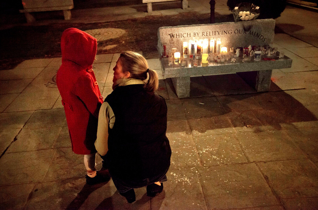 Description of . Rhonda Eleish, right, talks to her daughter Kari Ergmann, 6, both of Bridgewater, Conn., next to a candlelight vigil outside the Edmond Town Hall, Saturday, Dec. 15, 2012, in Newtown, Conn. Eleish suspects her daughter knew one of the victims of Friday's shooting at Sandy Hook Elementary School in Newtown that killed 26 people, including 20 children. (AP Photo/David Goldman)