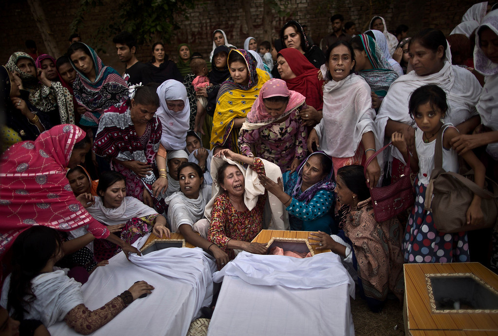 Description of . Pakistani women grieve over the coffins of their relatives, who were killed in a suicide attack on a church, in Peshawar, Pakistan, Sunday, Sept. 22, 2013.  (AP Photo/Muhammed Muheisen)
