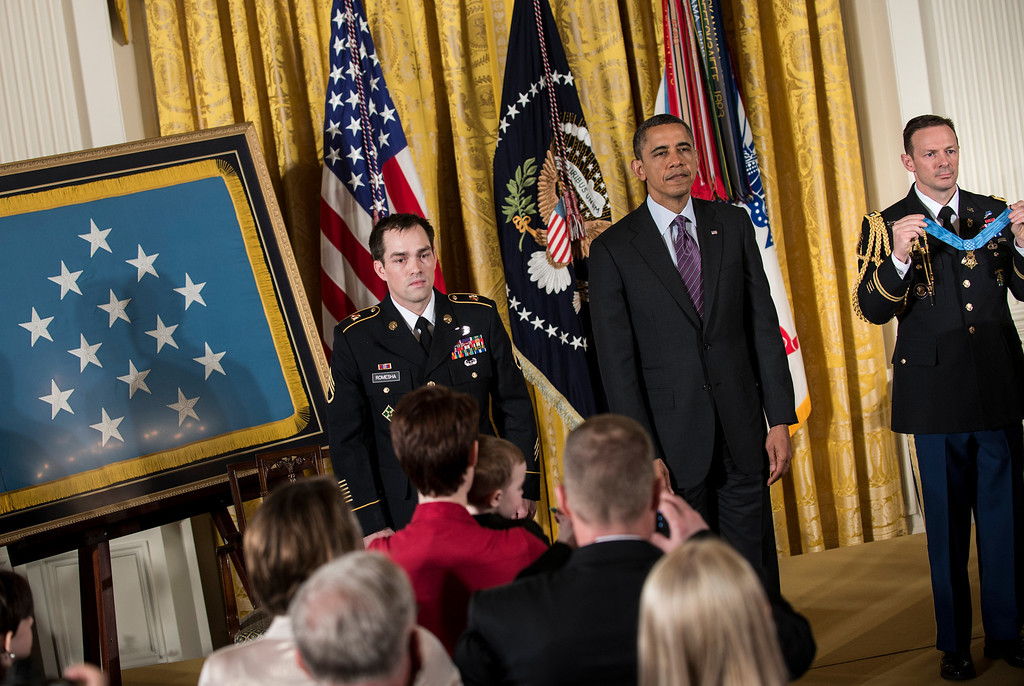 Description of . Former US Army Staff Sargent Clinton Romesha (L), US President Barack Obama and a military aid listen as a citation is read during a Medal of Honor ceremony in the East Room of the White House February 11, 2013 in Washington, DC.  AFP PHOTO/Brendan  SMIALOWSKI/AFP/Getty Images