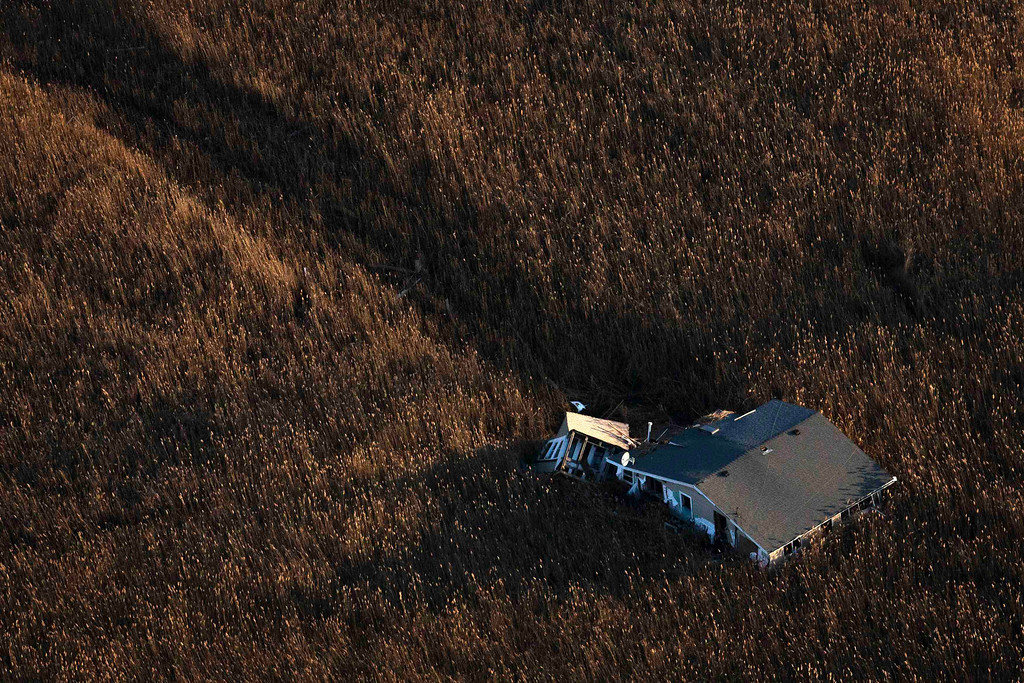 Description of . An aerial view shows a house pushed into marshland almost a month after the Oakwood neighborhood in the Staten Island borough of New York was left devastated by Hurricane Sandy, November 28, 2012. The storm killed 132, left thousands homeless and economic damages topping $50 billion. REUTERS/Adrees Latif