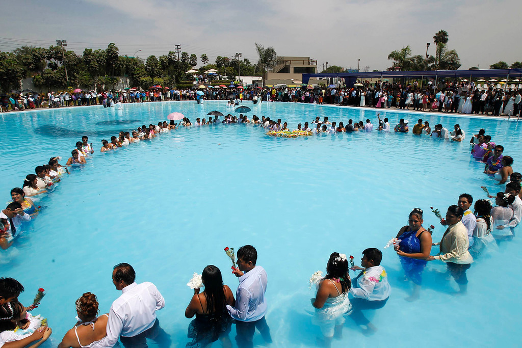 Description of . Newlywed couples make a heart's shape in a public swimming pool during a mass wedding on Valentine's Day in Lima February 14, 2013. About 200 couples married in the ceremony organized by a local municipality to commemorate Saint Valentine's Day. REUTERS/Enrique Castro-Mendivil