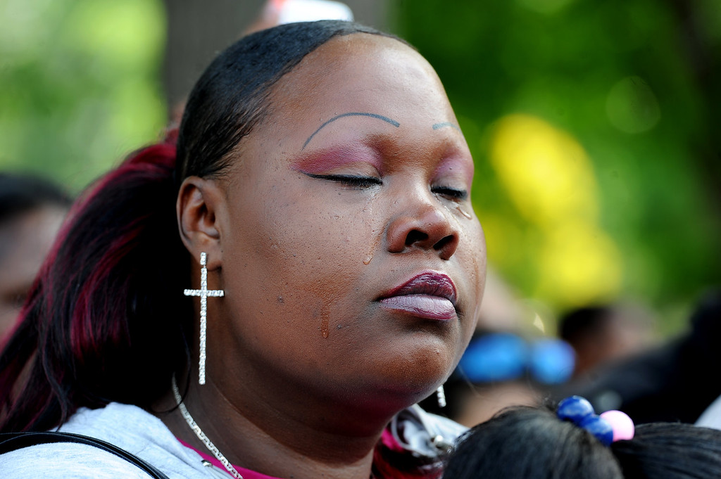 Description of . Tamesah Morris shed tears during the rally in City Park in Denver, CO on July 14, 2013.  Members of the African American community turned out for a rally  to show their disappointment in the acquittal of George Zimmerman in the murder trail of Trayvon Martin on July 14, 2013. Zimmerman is the Florida man who shot and killed Trayvon Martin.
