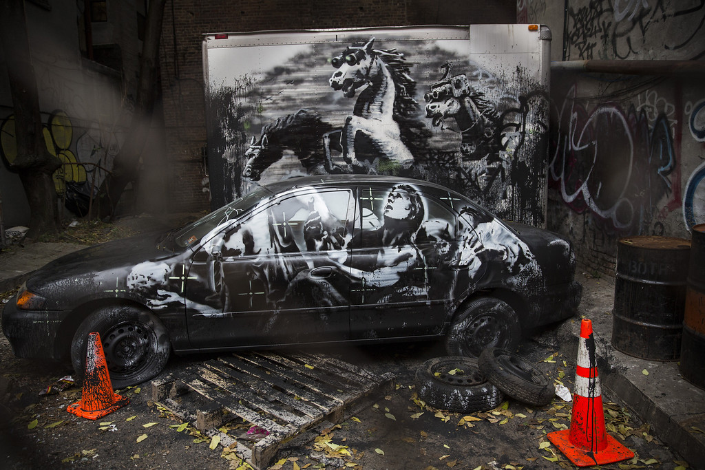 Description of . The latest work from street artist Banksy is seen through a chain link fence on October 9, 2013 in the Lower East Side neighborhood of New York City. Banksy is in the midst of creating a month long series of pieces of street art.  (Photo by Andrew Burton/Getty Images)