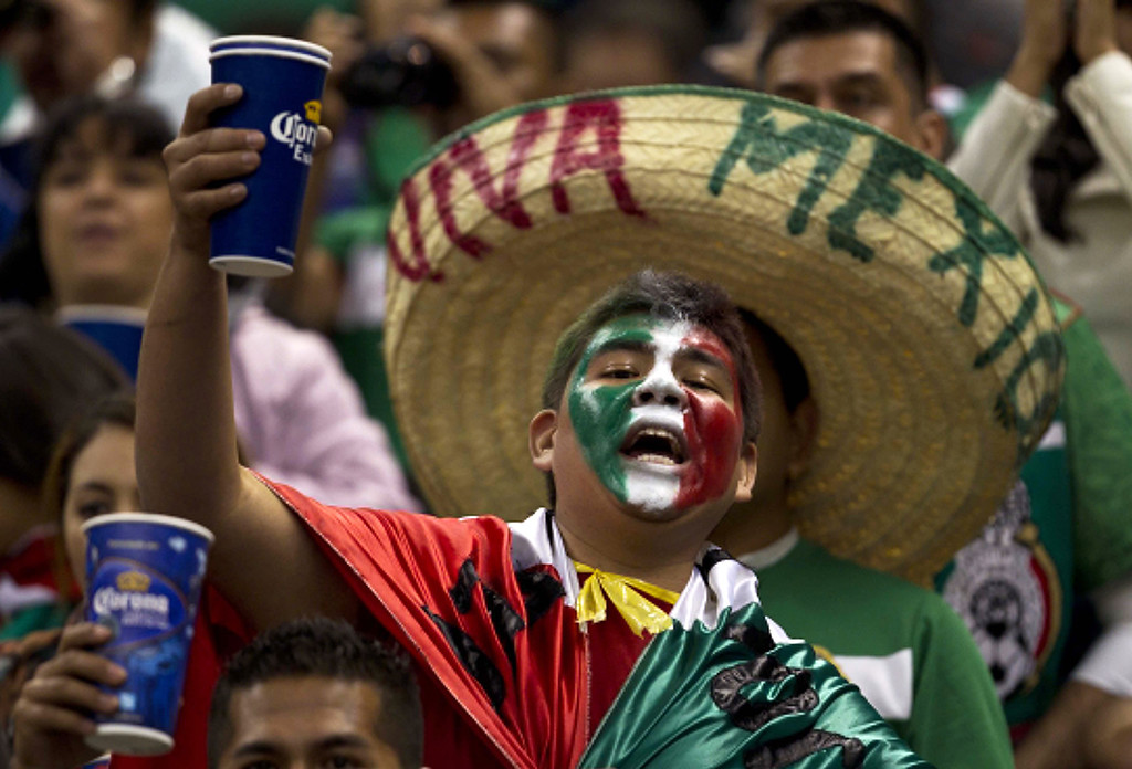 Description of . A Mexican fan cheers on his team before the start of a 2014 World Cup qualifying match against the United States at the Aztec stadium in Mexico City, Tuesday, March 26, 2013. (AP Photo/Christian Palma)
