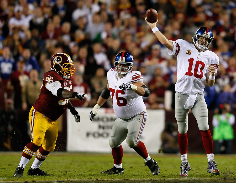 Description of . LANDOVER, MD - DECEMBER 03:  Quarterback  Eli Manning #10 of the New York Giants throws the ball as teammate Chris Snee #76 blocks Barry Cofield #96 of the Washington Redskins in the first half at FedExField on December 3, 2012 in Landover, Maryland.  (Photo by Rob Carr/Getty Images)
