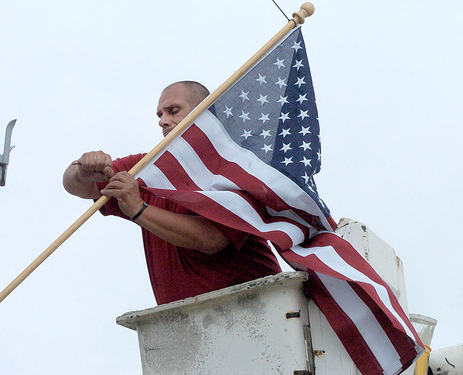 Description of . Wilkes-Barre DPW employee Dave Lewis installs an American flag on the Market Street Bridge, Thursday May 23, 2013 in Wilkes-Barre, Pa. in conjunction with veterans organizations for Memorial Day weekend. (AP Photo/The Citizens' Voice, Mark Moran)  MANDATORY CREDIT
