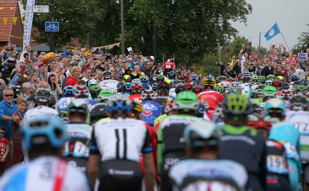 Description of . YORK, ENGLAND - JULY 06:  Throngs of fans await the peloton as they leave the start of stage two of the 2014 Le Tour de France from York to Sheffield on July 6, 2014 in York, United Kingdom.  (Photo by Doug Pensinger/Getty Images)