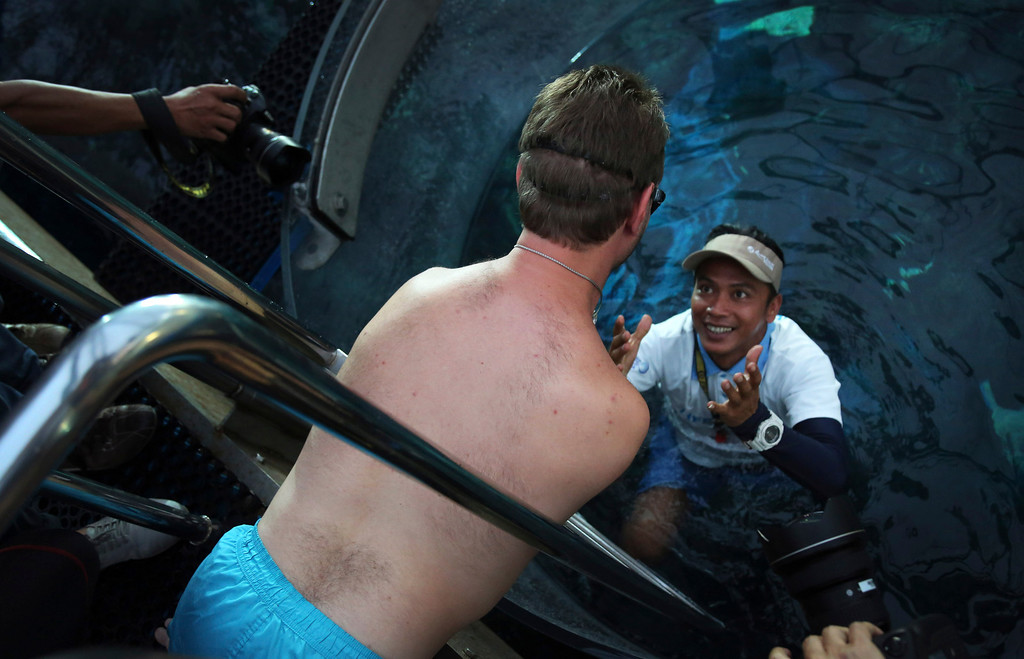 "Description of . Nick Vujicic surveys the acrylic enclosure submerged into a shark enclosure to keep him safe while diving among the sharks, Thursday, Sept. 5, 2013, in Singapore. Vujicic, a Serbian Australian evangelist and motivational speaker born with tetra-amelia syndrome, a rare disorder characterized by the absence of all four limbs, is in the city-state to give a motivational talk and was visiting  ""The Shark Encounter at Marine Life Park\"" at one of Singapore\'s main tourist attractions in Resorts World Sentosa. (AP Photo/Wong Maye-E)"