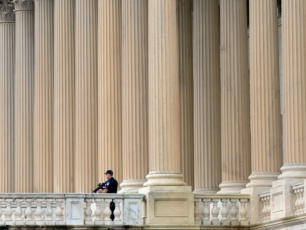 Description of . U.S. Capitol Police personnel keep watch on the East Plaza of the Capitol as the investigation continues to the shooting at the nearby Washington Navy Yard  Monday, Sept. 16, 2013, in Washington. At least one gunman opened fire inside a building at the Washington Navy Yard on Monday morning.  (AP Photo/J. Scott Applewhite)