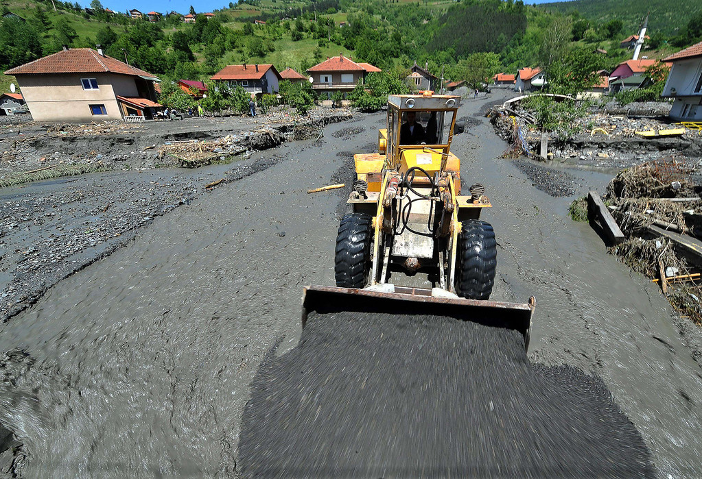 Description of . A worker uses  a bulldozer to clear the earth after a landslide in the flooded village of Topcic Polje, near the northern Bosnian city of Doboj, on May 19, 2014, after the river Bosna flooded entire agricultural fields and several urban areas along its flow during the weekend's rainfall, which also caused landslides. AFP PHOTO / ELVIS BARUKCIC/AFP/Getty Images