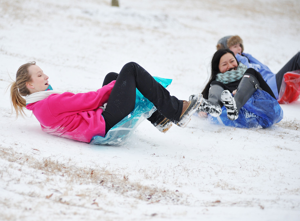 Description of . University of Mississippi students Shelby Nordan, left, Nancy Truong, center, and Kathryn Davis slide down a hill, in Oxford, Miss. on Tuesday, Feb. 11, 2014. Due to a thin layer of ice covered by snow that fell overnight, the university is closed until noon Tuesday. (AP Photo/Oxford Eagle, Bruce Newman)