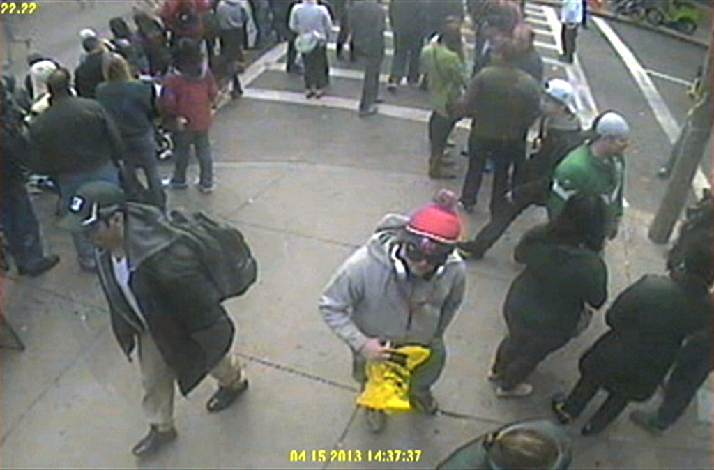 Description of . This image released by the FBI on Thursday, April 18, 2013, shows in a image from video what the FBI are calling suspect number 1, front left, in black cap, and suspect number 2, in white cap, back right, walking near each other through the crowd in Boston on Monday, April 15, 2013, before the explosions at the Boston Marathon. (AP Photo/FBI)