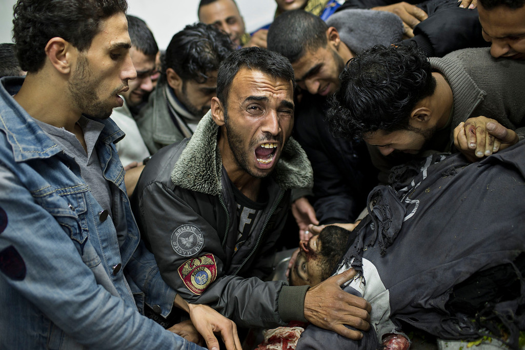 Description of . In this Nov. 18, 2012 file photo, a Palestinian man cries next the body of a dead relative in the morgue of Shifa Hospital in Gaza City. This photo was one in a series of images by Associated Press photographer Bernat Armangue that won the first place prize in the World Press Photo 2013 photo contest for the Spot News series category.  (AP Photo/Bernat Armangue, File)