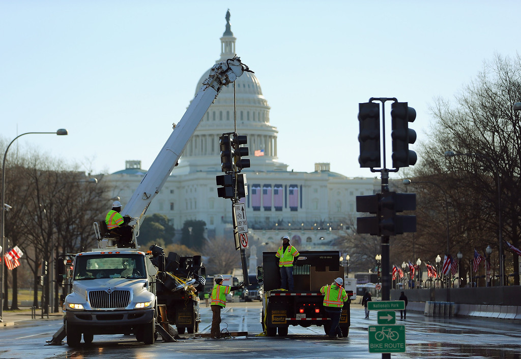 Description of . Workers from M.C. Dean Company remove the street lights along Pennsylvania Ave as they prepare for the Inauguration Parade on January 20, 2013 in Washington, DC.  The US capital is preparing for the second inauguration of US President Barack Obama, which will take place on January 21.  (Photo by Joe Raedle/Getty Images)