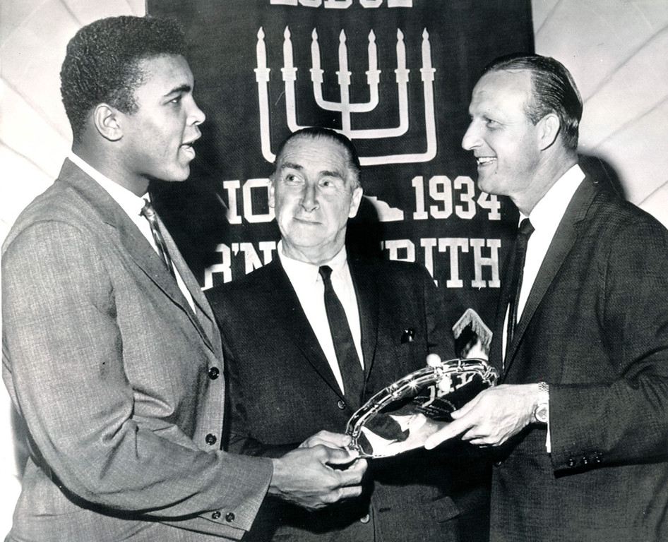 Description of . Cassius Clay, heavyweight boxing challenger, (left) and Stan Musial of the St. Louis Cardinals, (right) receive awards at the annual B'nai B'rith sports dinner in Boston tonight.  Making the awards is Horace McMohn, star of the television show, 'Naked City.' 1962. Credit: AP
