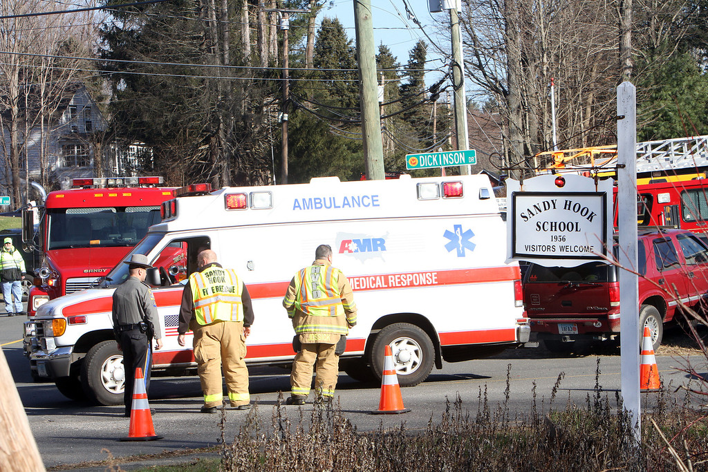 Description of . Ambulances leave the Sandy Hook Elementary School following a shooting at the school, Friday, Dec. 14, 2012 in Newtown, Conn. A man opened fire inside the Connecticut elementary school where his mother worked Friday, killing 26 people, including 18 children, and forcing students to cower in classrooms and then flee with the help of teachers and police. (AP Photo/The Journal News, Frank Becerra Jr.)