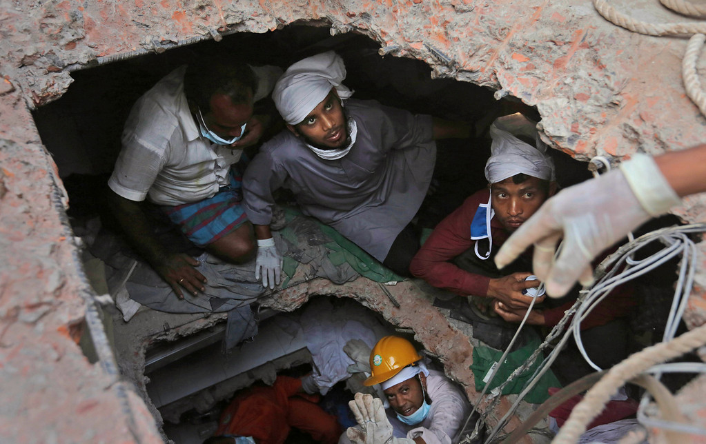 Description of . In this April 28, 2013 file photo, Bangladeshi rescue workers search for survivors as they are seen through a hole in the roof a building that collapsed Wednesday in Savar, near Dhaka, Bangladesh.  (AP Photo/Kevin Frayer File)