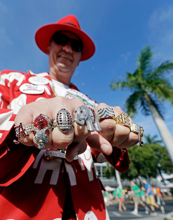 Description of . Robin Albano of Decatur, Ala., shows off his rings outside Sun Life Stadium before the BCS National Championship college football game between the Alabama and the Notre Dame Monday, Jan. 7, 2013, in Miami. (AP Photo/Chris O'Meara)