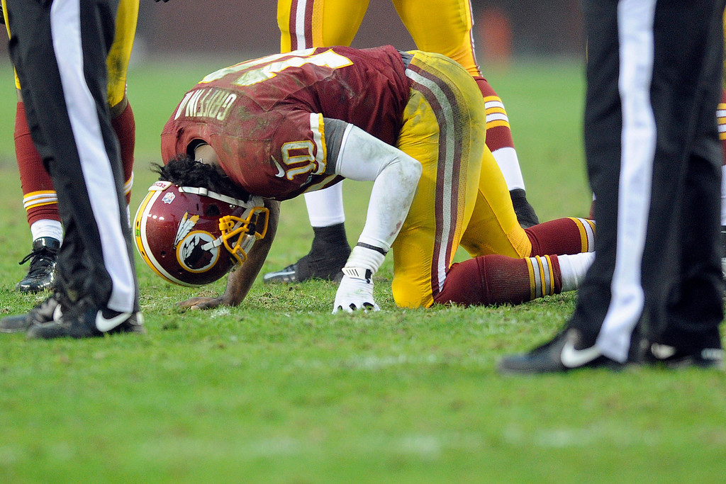 Description of . Washington Redskins quarterback Robert Griffin III kneels on the ground after an injury during the second half of an NFL football game against the Baltimore Ravens in Landover, Md., Sunday, Dec. 9, 2012. (AP Photo/Nick Wass)