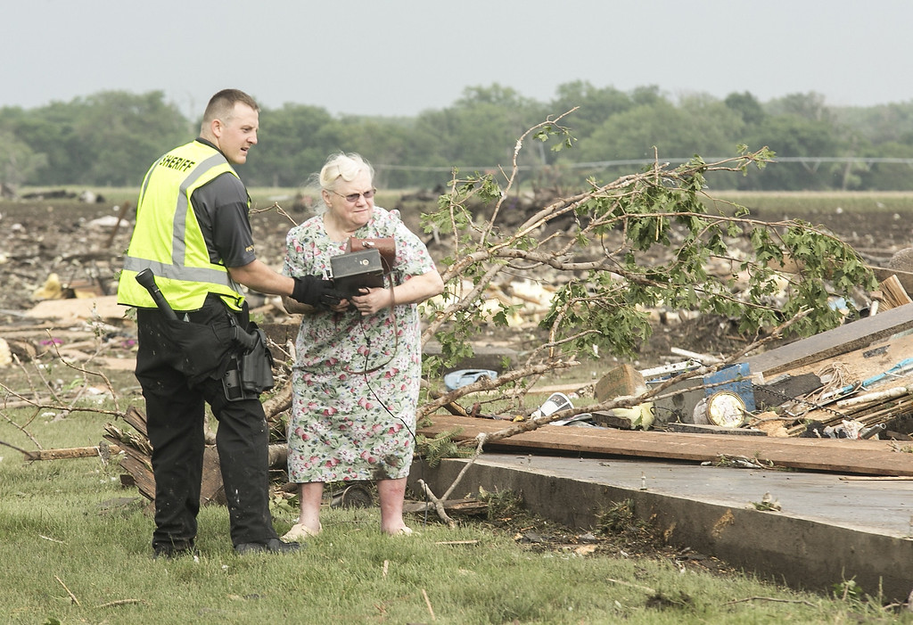 Description of . Ruth Labenz is assisted to safety by a Stanton County Sherriff's officer after her home was destroyed in the town of Pilger, Neb. Monday, June 16, 2014. At least one person is dead and at least 16 more are in critical condition after two massive tornadoes swept through northeast Nebraska on Monday. (AP Photo/Mark 'Storm' Farnik)