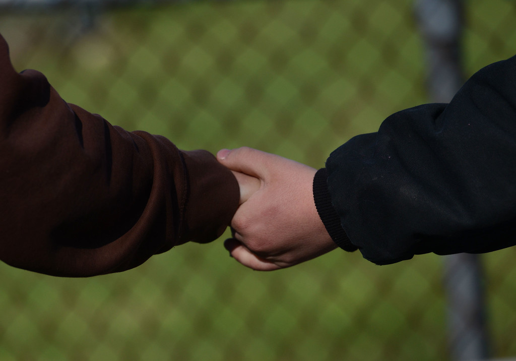 Description of . A parent holds hands with a Franklin Regional High School while picking up the student after more than a dozen students were stabbed by a knife wielding suspect at the school on Wednesday, April 9, 2014, in Murrysville, Pa., near Pittsburgh. The suspect, a male student, was taken into custody and is being questioned. (AP Photo/Tribune Review, Sean Stipp)