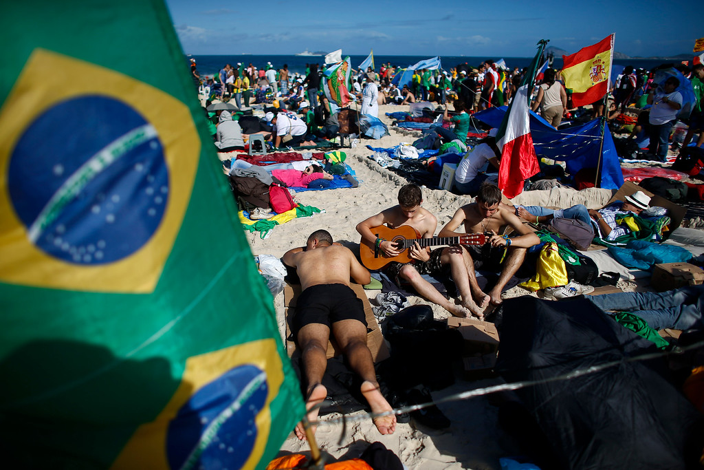 Description of . Pilgrims play guitar and sing near a Brazilian flag, left, and a Spanish flag, right, on Copacabana beach in Rio de Janeiro, Brazil, Saturday, July 27, 2013. Pope Francis will preside over an evening vigil service on Copacabana beach that is expected to draw more than 1 million young people. (AP Photo/Victor R. Caivano)