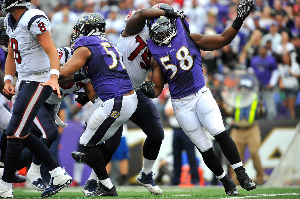 Description of . Outside linebacker Elvis Dumervil #58 of the Baltimore Ravens is held as he rushes the Houston Texans quarterback, penalty not called, at M&T Bank Stadium on September 22, 2013 in Baltimore, Maryland. The Ravens defeated the Texans 30-9. (Photo by Larry French/Getty Images)