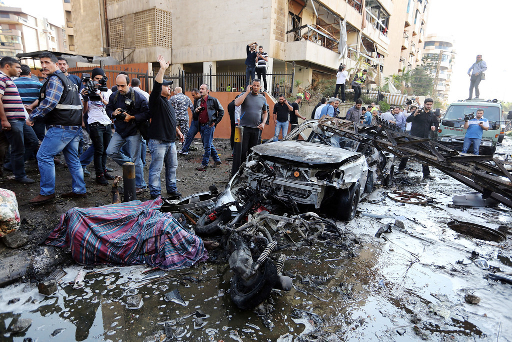 Description of . Lebanese people gather at the scene where two explosions have struck near the Iranian Embassy killing many, in Beirut, Lebanon, Tuesday, Nov. 19, 2013.  (AP Photo/Bilal Hussein)