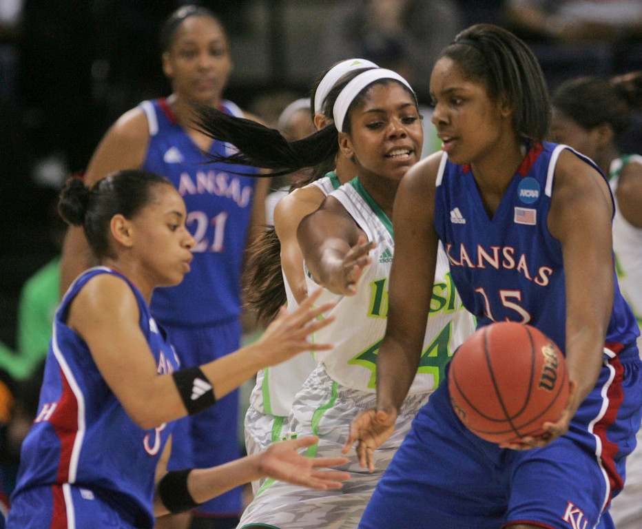 Description of . Kansas forward Chelsea Gardner (15) passes the ball to Kansas guard Angel Goodrich, left, as Notre Dame forward Ariel Braker (44) pressures during the first half a regional semi-final of the NCAA college basketball tournament Sunday, March31, 2013, in Norfolk, Va.  (AP Photo/Jason Hirschfeld)