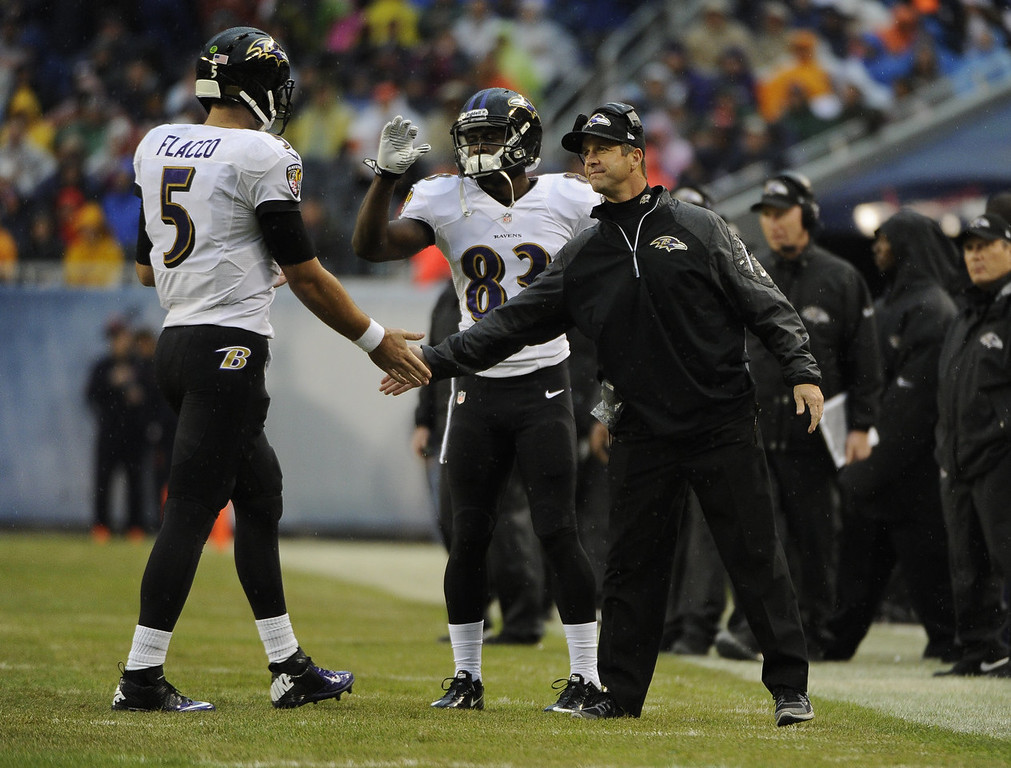 Description of . Head coach John Harbaugh of the Baltimore Raven congratulates Joe Flacco #5  after a Ravens touchdown against the Chicago Bears during the first quarter Ravensson November 17, 2013 at Soldier Field in Chicago, Illinois. (Photo by David Banks/Getty Images)