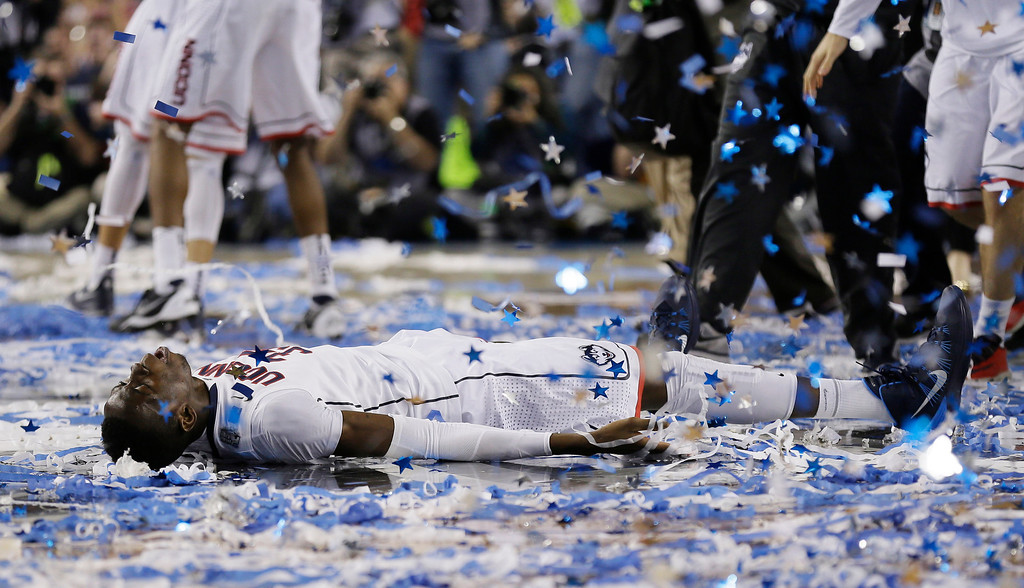 Description of . Connecticut center Amida Brimah celebrates after winning the NCAA Final Four tournament college basketball championship game 60-54, against Kentucky Monday, April 7, 2014, in Arlington, Texas. (AP Photo/Charlie Neibergall)