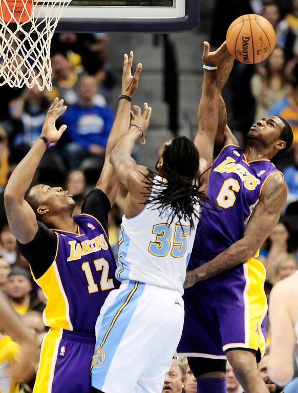 Description of . Los Angeles Lakers' Dwight Howard (L) and Earl Clark (R) block Denver Nuggets' Kenneth Faried during their NBA basketball game in Denver, Colorado February 25, 2013.   REUTERS/Mark Leffingwell