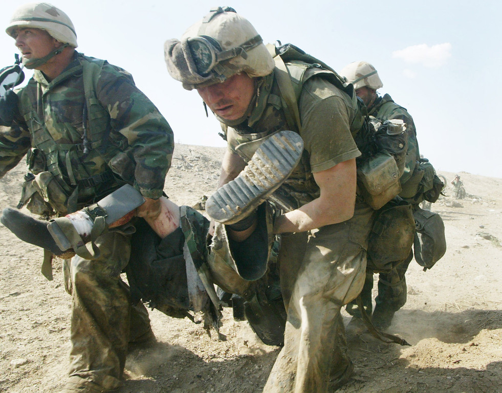 Description of . U.S. Marines from Task Force Tarawa carry a wounded Marine during a gun battle March 23, 2003 in the southern Iraqi city of Nasiriyah. The Marines suffered a number of deaths and casualties during gun battles throughout the city. (Photo by Joe Raedle/Getty Images)