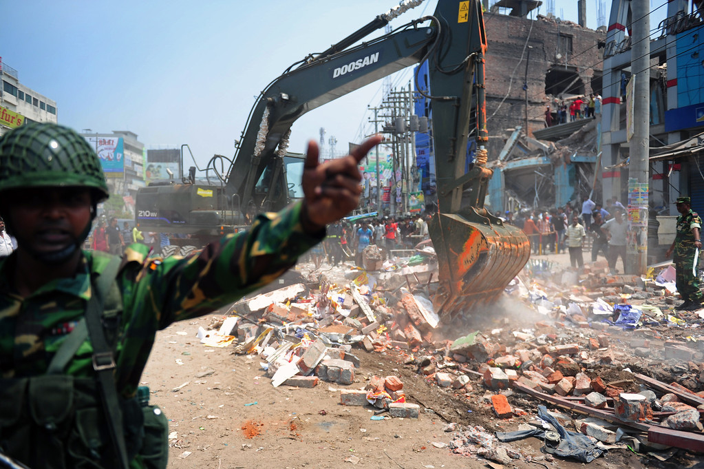 Description of . Bangladeshi Army personnel assist in rescue operations after an eight-story building collapsed in Savar, on the outskirts of Dhaka, on April 24, 2013.  AFP PHOTO/Munir UZ ZAMAN/AFP/Getty Images